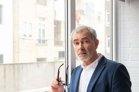 white haired adult or senior man next to window with natural light