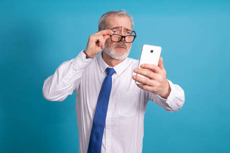 isolated businessman with glasses looking at mobile phone