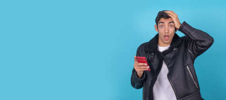 young man with mobile phone isolated on color background