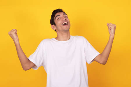 young teenager man with jubilant expression isolated on color background