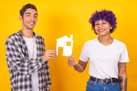 young couple with house isolated on color background