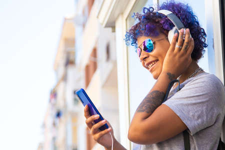 afro american latin girl with mobile phone and headphones on the street outdoors