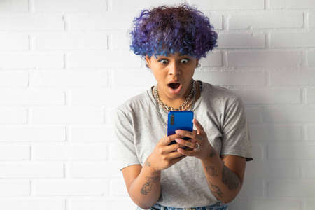 young woman afro american with smartphone on the wall