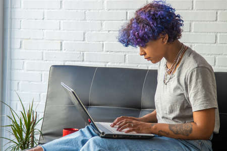 young african american woman using laptop on sofa at home