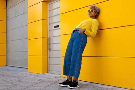 fashionable young girl leaning on yellow street wall