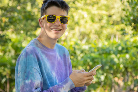 young teenager outdoors with mobile phone and sunglasses