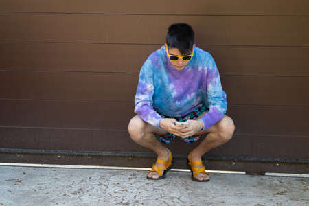 teenager or male student with mobile phone and sunglasses