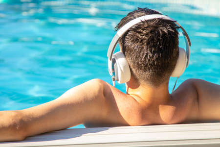 young man with headphones in the pool listening to music