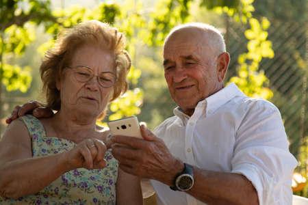 senior couple looking at mobile phone Foto de archivo