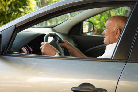 portrait of senior male driving car