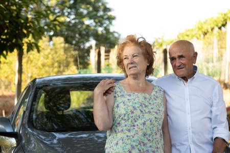 portrait of senior couple with car outdoors