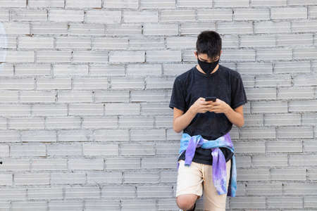 young teenager with sanitary mask and mobile phone on the street wall 스톡 콘텐츠