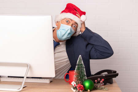 businessman on christmas in office with face mask for coronavirus pandemic