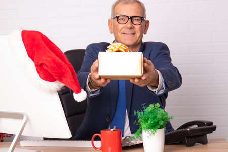 businessman in office at christmas with gift box