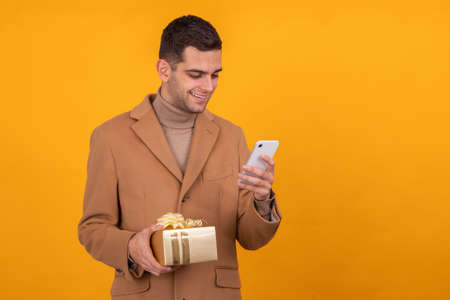 man with gift box and mobile phone isolated 스톡 콘텐츠