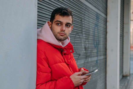 young man with mobile phone leaning on the wall in the street