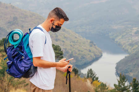 young man protected with mask hiking in the mountains with mobile phone Banco de Imagens