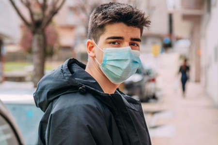 teenage boy with face mask on the street Stock fotó