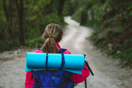 woman with backpack hiking on the road Foto de archivo