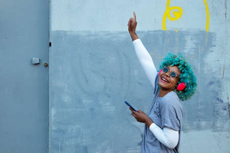 afro american woman dancing in the street smiling with phone and headphones