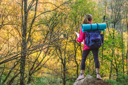woman with backpack and map in nature Foto de archivo