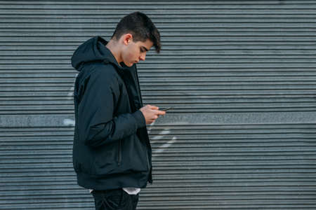 young urban casual style teenager on the street outdoors with mobile phone