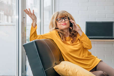 dissatisfied woman talking on mobile phone at home