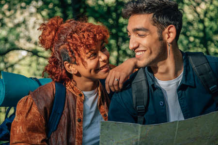 multicultural young couple with map and travel backpack