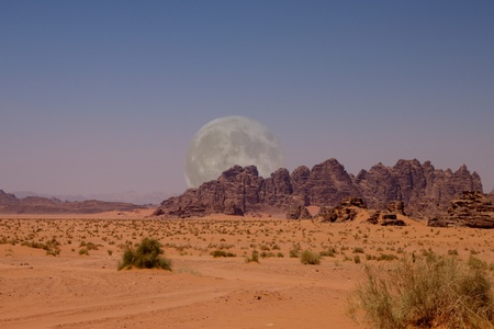 View of the desert of Wadi Rum with big moon in southern Jordan photo