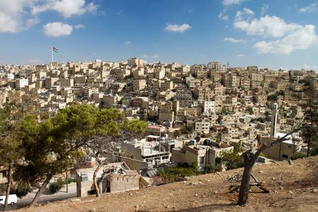 Panoramic view of the city of Amman with Jordanian flags of the royal palace in the background photo