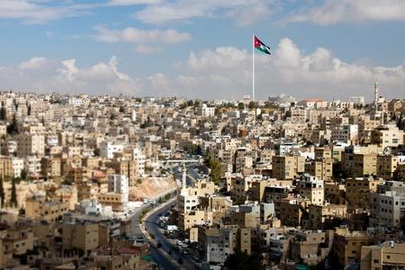 the citadel: Vista panoramica della citt� di Amman con bandiere giordane