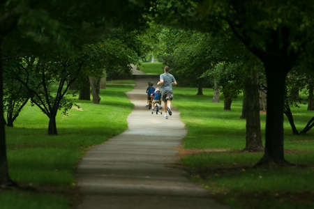 father jogging, two sons biking on path in city park