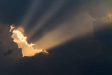 sun rays shining through dark cloud