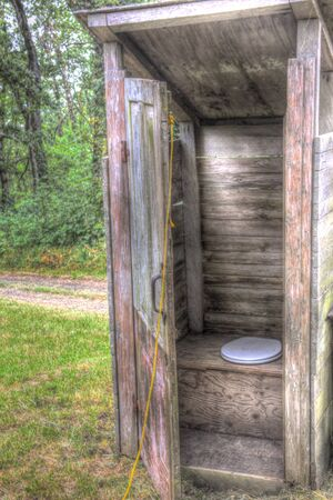 old wood outhouse with open door