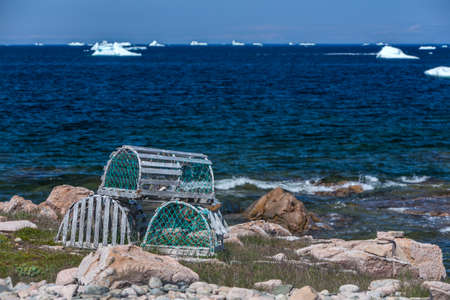 lobster traps on rocks by ocean with icebergs; Fogo Island, Newfoundland