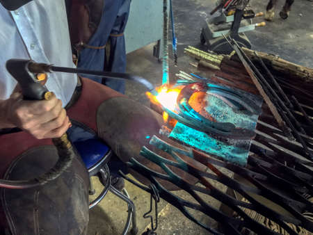 blacksmith working on horseshoe with torch
