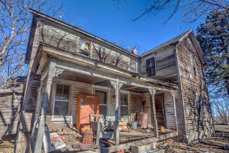 abandoned wood house with objects on front porch, rural Kansas Stock Photo