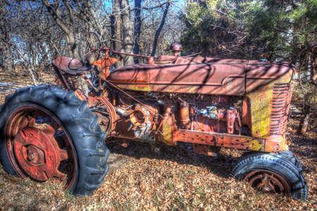 abandoned old red tractor in leaves, rural Kansas Banco de Imagens