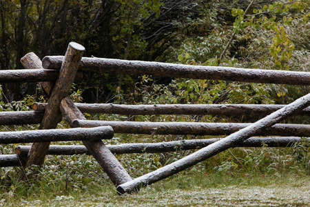 wood rail fence covered with light snow; Wyoming
