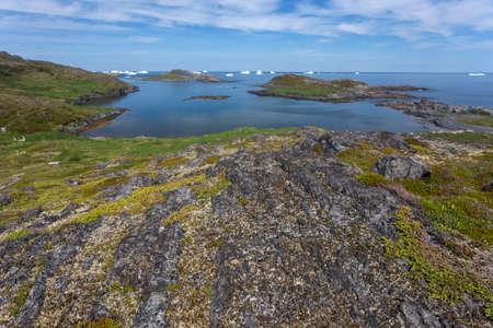Rocky Newfoundland coastline on Fogo Island; distant icebergs