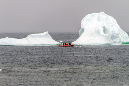 iceberg with small red tourist boat, Newfoundland