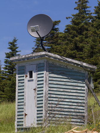 old weathered outhouse with satellite dish on roof, Newfoundland Banque d'images - 133204264