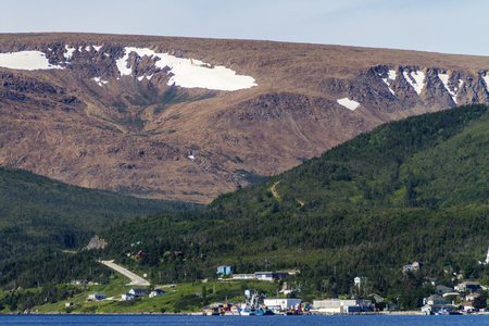 The Tablelands with snow above town of Woody Point, Newfoundland Banque d'images - 133204388