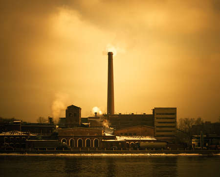 ozone: Old factory from a red bricks. Environmental pollution and destruction of ozonosphere.