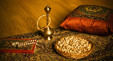 Evening in east style. The rest on the rug with almonds, hookah and book. Stock Photo