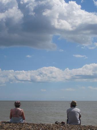 pepples: Couple on Beach Looking Out To Sea  Stock Photo