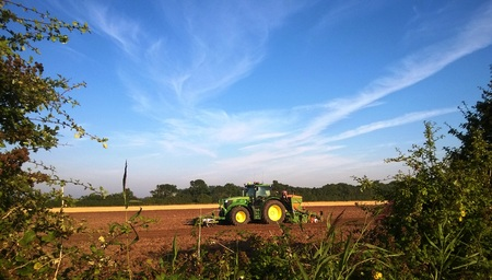 ploughing: A Tractor Ploughing the land in rural England in Summer