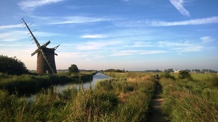 Landscape of Horsey windmill on the Norfolk Broads with man Фото со стока