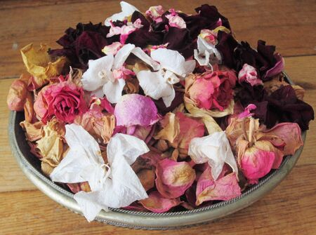 pinks: A bowl of dried rose petals in shades of pink, red, cream and white Stock Photo