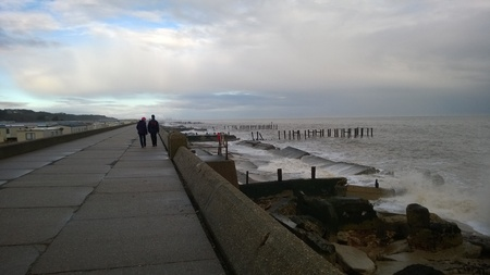 defenses: Couple Walk by coast at Lowestoft, Suffolk, England on Winters Day by Sea Defenses